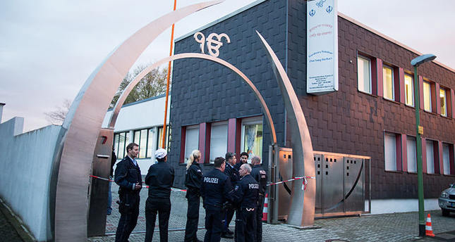Police officers stand in front of a Sikh temple after three people have been injured in an apparently deliberate explosion Saturday evening, April 16, 2016 in the western German city of Essen.  A spokesman for Essen police told The Associated Press that a masked person is reported to have fled the scene shortly after the blast. (Marcel Kusch/dpa via AP)