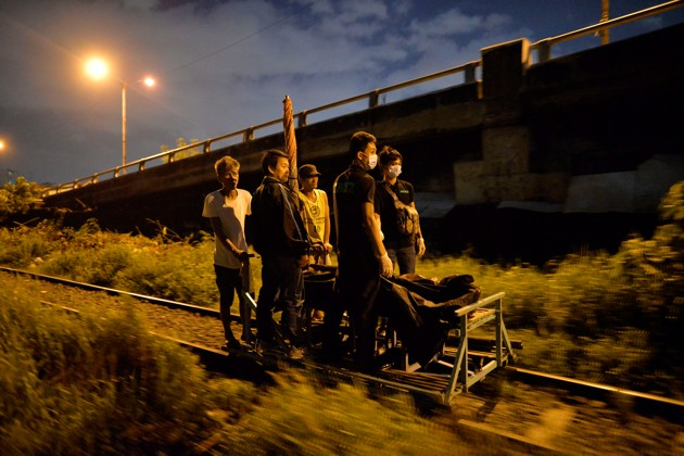 """Residents transport on a trolley two bodies of men, after police said they were killed by policemen after they fought back during an illegal drugs """"Shabu"""" (Meth) operation in Manila, Philippines August 18, 2016.  REUTERS/Ezra Acayan - RTX2LNMB"""