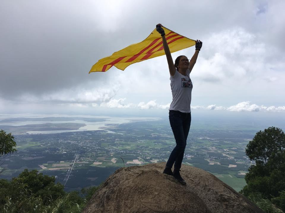 Một cô gái với lá cờ ba sọc đỏ tung bay trên đỉnh núi (ảnh; Facebook Hong Thai Hoang)